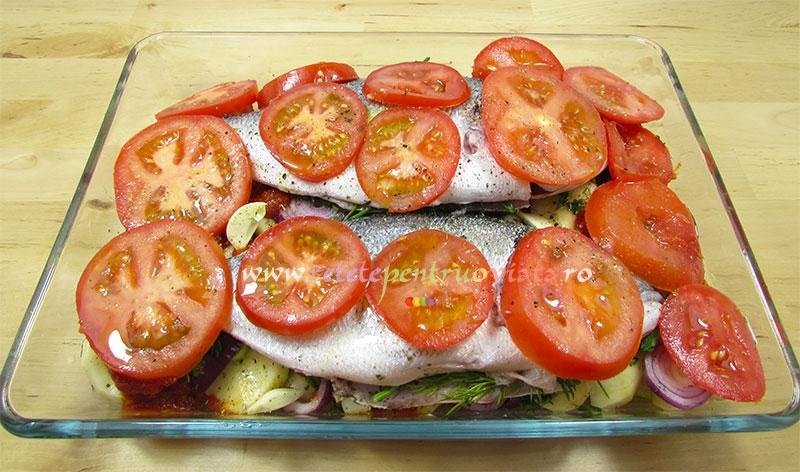 Reteta de peste la cuptor cu cartofi si rosii - asezam pestele peste stratul de legume si il acoperim cu felii de rosii